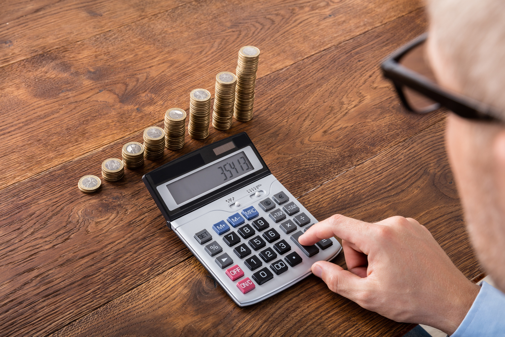 Person Hand Doing Calculation On Stacked Coin And Piggybank At Wooden Desk. Income Tax Concept